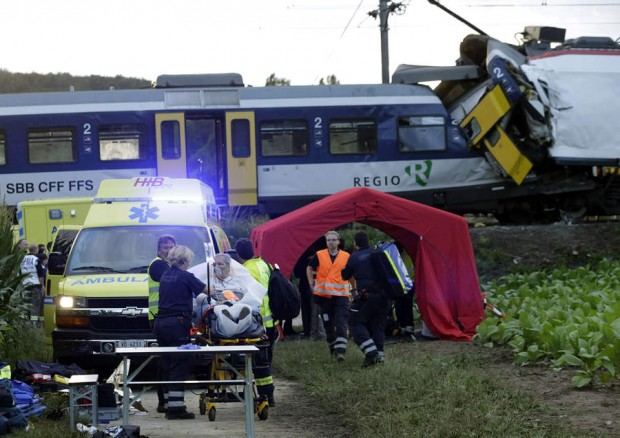 Rescue workers transport a wounded person on a stretcher after a head on collision between two trains near Granges-pres-Marnand