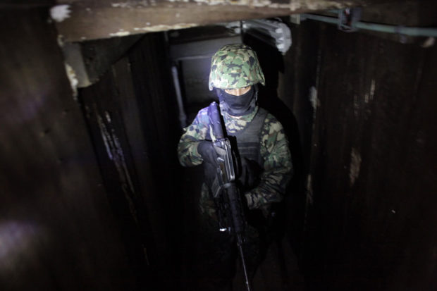 A Mexican Marine stands in the city's drainage system after walking through a connecting tunnel during a presentation for the media n Culiacan