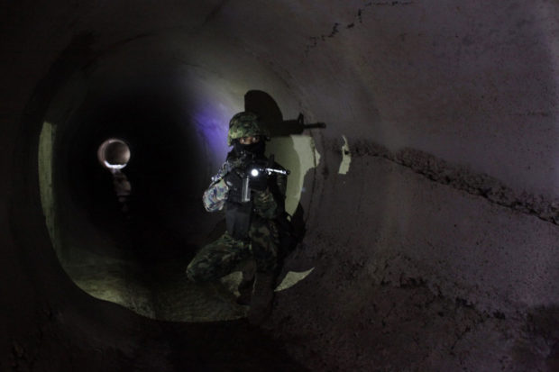 A Mexican Marine points his weapon in the city's drainage system after walking through a connecting tunnel underneath the houses of Mexican kingpin Guzman during a presentation for the media in Culiacan