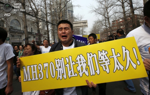 A family member of a passenger aboard Malaysia Airlines MH370 cries during a protest in Beijing