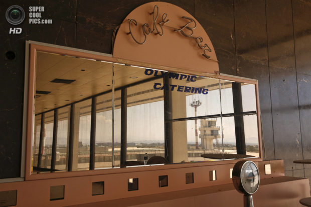 An auxiliary control tower is reflected in a mirror at a deserted cafe in the east terminal of the former Athens International airport, Hellenikon